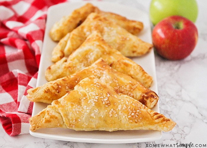 a long white serving tray with six golden brown apple turnovers on it in a line