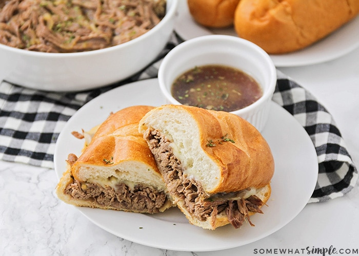 a french dip sandwich cut in half and stacked on a white plate with a side of au jus in a small white bowl. Behind the plate is a bowl filled with shredded beef and a plate with French rolls on it.