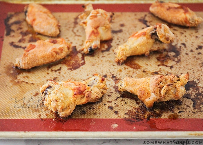 several garlic parmesan chicken wings on a baking sheet taken right out of the oven