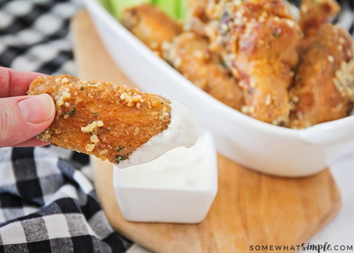a chicken wing backed in garlic and parmesan being dipped in a side of ranch dressing. A bowl of several chicken wings are in the background.