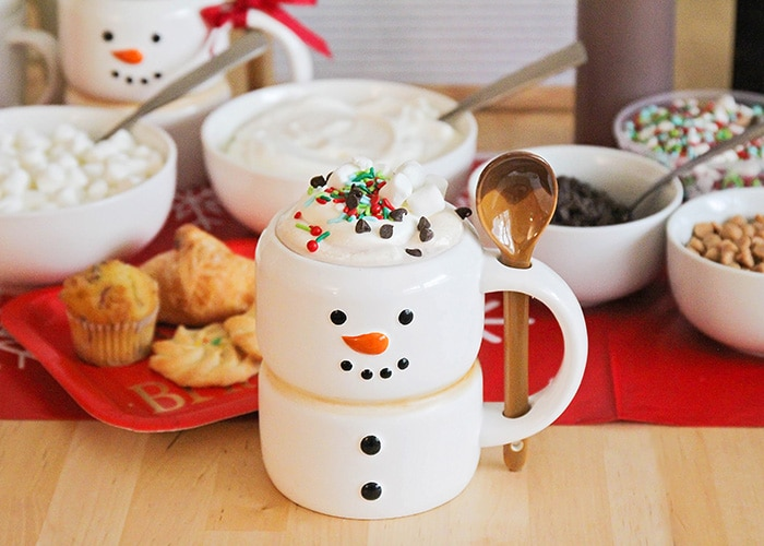 a hot cocoa bar with a snowman mug filled with hot chocolate