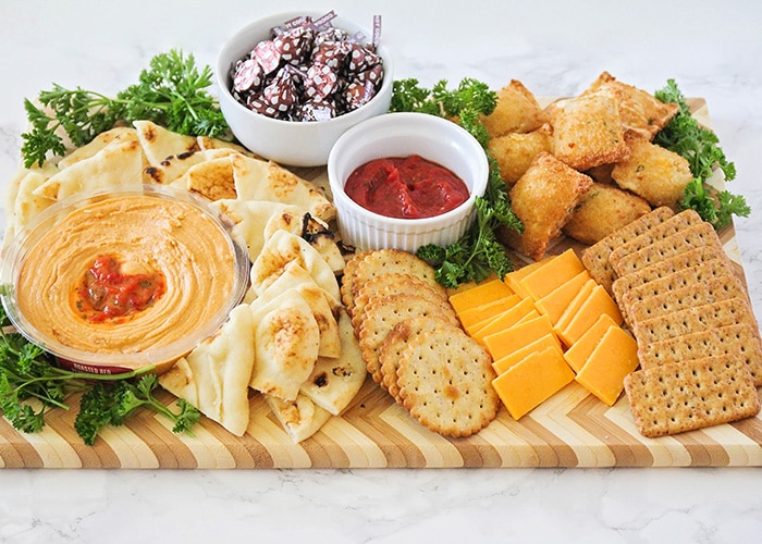 An easy to assemble kid friendly appetizer board that is filled with slices of flatbread, various crackers, slices of cheddar cheese, baked pizza bites surrounded by parsley with a white dish filled with Hershey's kisses, another white dish in the middle filled with marinara sauce and a small glass bowl filled with hummus.