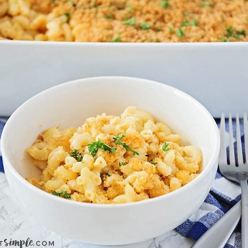 a white bowl filled with baked macaroni and cheese topped with bread crumbs and parsley. Behind the bowl is a casserole pan filled with more macaroni and cheese. Next to the bowl are two forks in a crossed patter laying on top of a blue and white checkered cloth napkin.