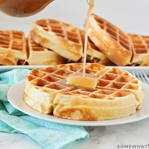 a Belgian waffle on a white plate topped with a pad of butter. Maple syrup is being poured from above onto the waffle. Behind the plate on the counter is a long serving tray filled with additional golden brown Belgian waffles.