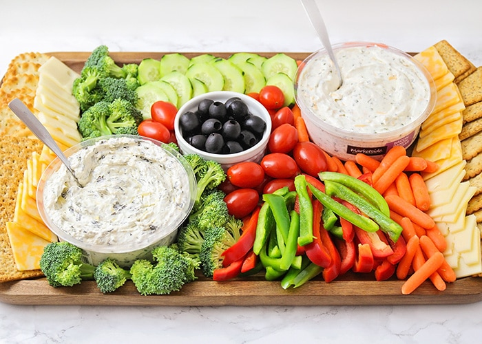 a colorful veggie tray idea that's filled with crackers, cheese, broccoli pieces, cucumber slices, cherry tomatoes, olives, red and green bell pepper slices, baby carrots and two vegetable dips all on a dark acacia wood serving tray.