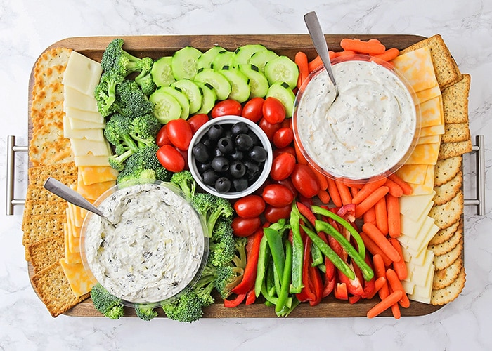 looking down on a simple and colorful veggie party tray idea that's filled with crackers, cheese, broccoli pieces, cucumber slices, cherry tomatoes, olives, red and green bell pepper slices, baby carrots and two vegetable party tray dips all on a dark acacia wood serving tray.