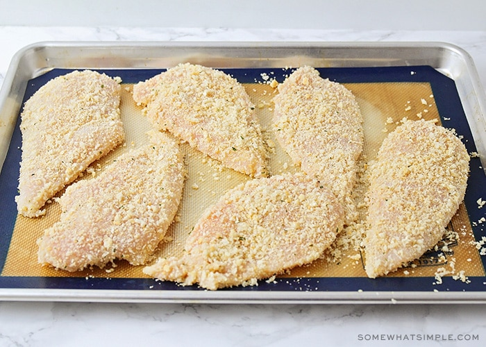 six uncooked chicken breast on a baking sheet covered in panko and bread crumbs