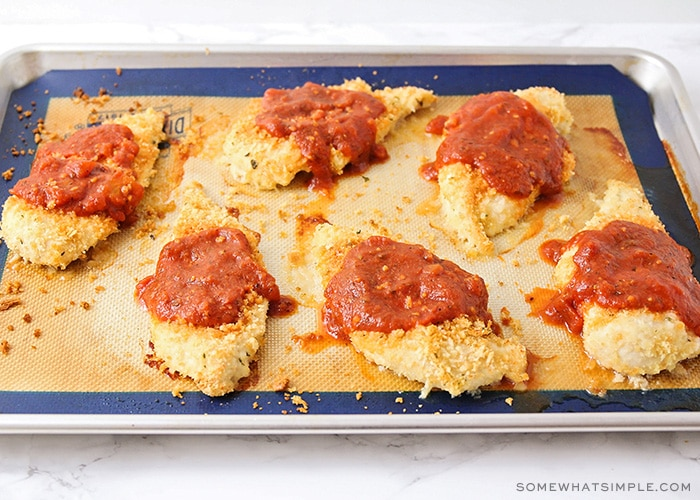 six baked chicken breasts with bread crumbs topped with marinara sauce that was put on the chicken after baking