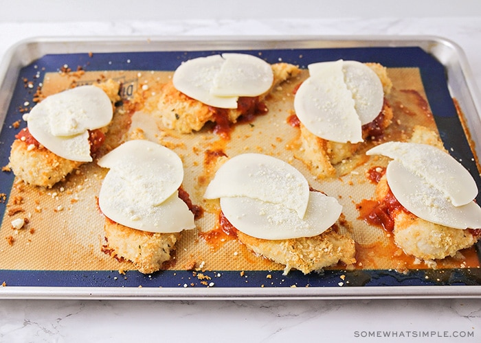 six baked chicken breasts on a baking sheet topped with marinara sauce and slices of provolone cheese placed on top