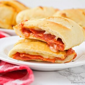 a homemade pepperoni pizza pocket that has been cut in half and the two halves are stacked on top of each other. In the background is a tray filled with several more golden brown pizza pockets.