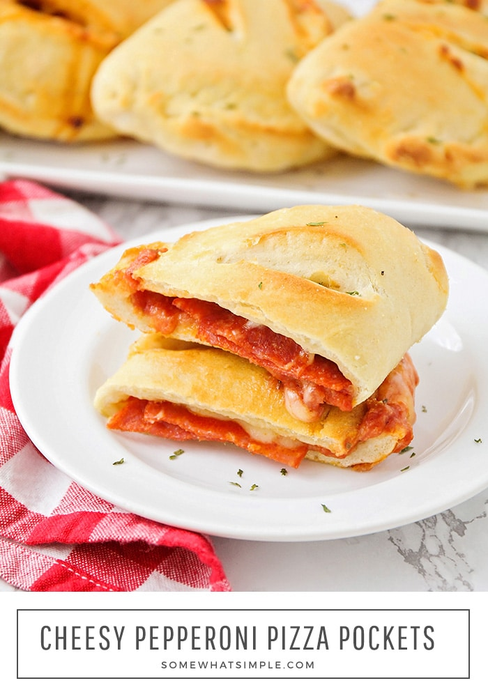 These cheesy pepperoni pizza pockets are a fun, and much less messy, way to enjoy pizza at home!  Baked in a homemade dough and filled with your favorite toppings, these pockets are perfect to eat at home or take with you on the go. #pizzapockets #homemadepizzapockets #pizzapocketswithpizzadough #pepperonipizzapockets #easypizzapockets via @somewhatsimple