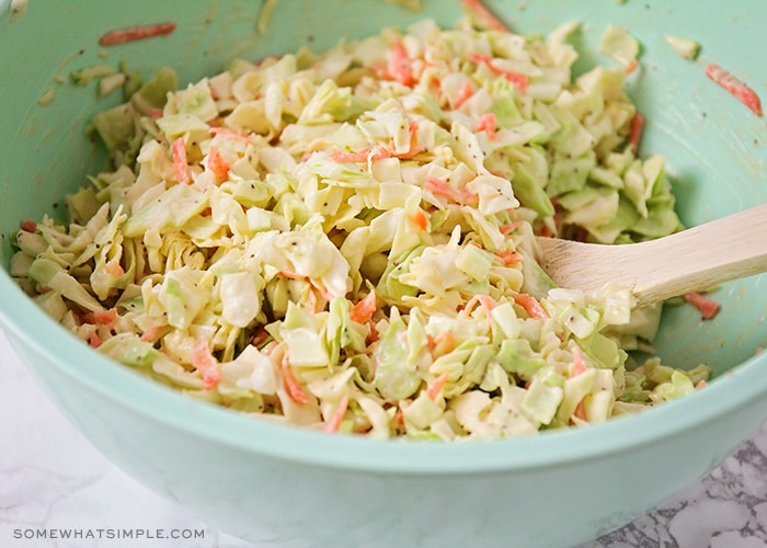 a light blue bowl filled with this homemade coleslaw recipe filled with cabbage, carrots and a homemade dressing