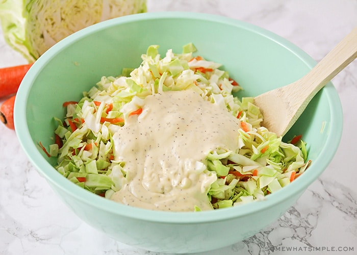 a bowl of coleslaw with homemade coleslaw dressing poured in the middle of the cabbage. A wooden spoon is in the bowl ready to mix the coleslaw and the dressing together.