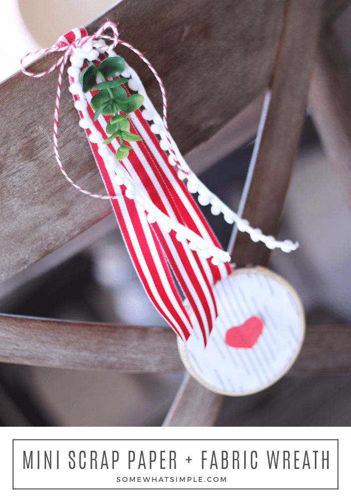 Dig through your scrapbook supplies and fabric stash to make this darling mini wreath that would look so festive anywhere in your home! #wreath #valentinedecor #craft #valentinesday #miniwreath