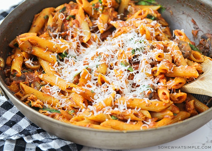 a large skillet filled with this chicken parmesan pasta recipe and topped with freshly grated parmesan cheese