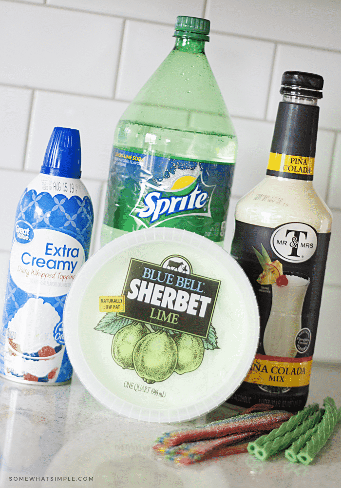 the ingredients to make a shamrock float; a bottle of sprite, a can of whipped cream, lime sherbet, pina colada mix and green licorice