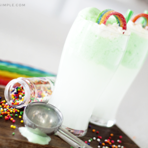 two green st. patrick's day drinks on a cutting board topped with a rainbow candy and a green piece of licorice for a straw. There are colored sprinkles spilled on the cutting board with an ice cream scoop laying next to the drink and colored pieces of licorice in the background.