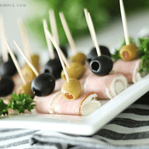 ham and cream cheese roll ups topped with black and green olives on a white serving tray