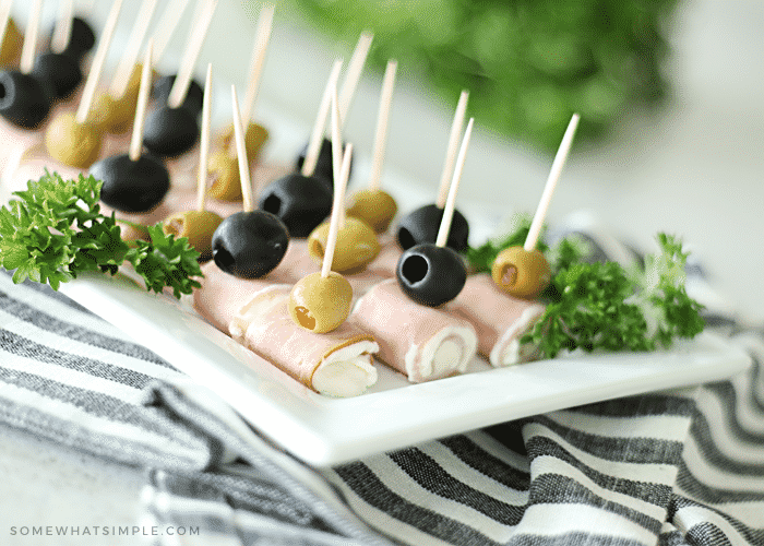 close up of cream cheese ham roll ups with green and black olives on a white plate