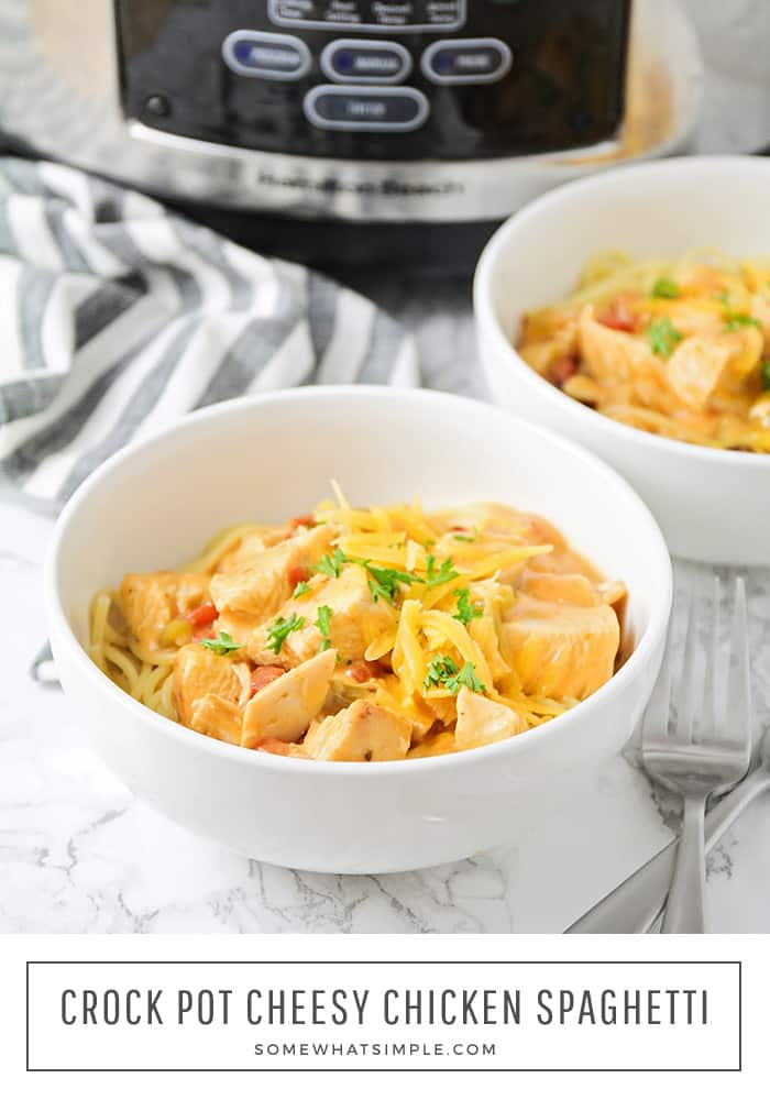 a bowl of chicken and cheese spaghetti topped with parsley that was made in the crock pot. In the background behind the bowl is a second bowl filled with spaghetti and a slow cooker. At the bottom of the image in a white box are the words crock pot cheesy chicken spaghetti.