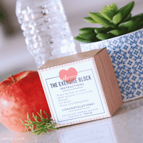 an exercise block with a funny printable on the outside sitting on a counter next to a bottle of water and an apple