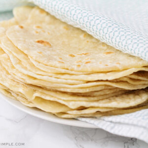 a stack of homemade flour tortillas wrapped in a blue and white towel on a white plate