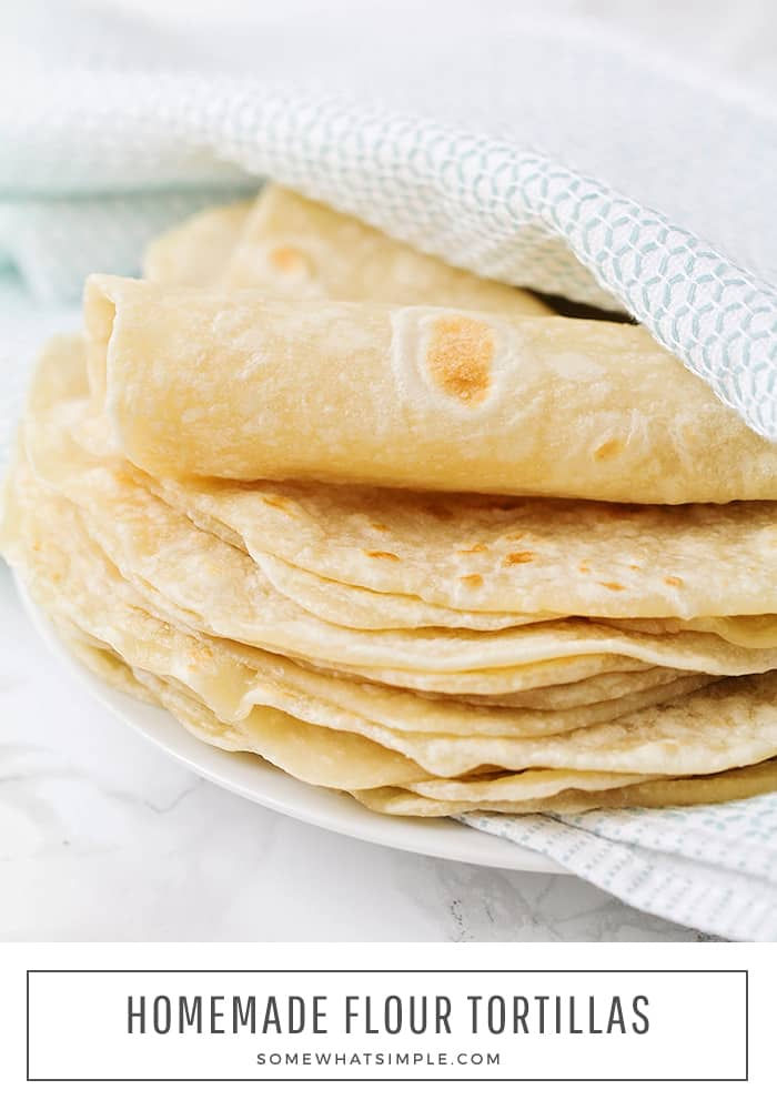 a stack of fresh flour tortillas wrapped in a blue and white towel on a white plate. At the bottom of the image in a white box are the words Homemade Flour Tortillas
