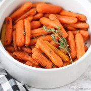 a white serving bowl that is filled with honey glazed carrots that have been baked and topped with thyme. A black and white checkered napkin is laying next to the bowl on the counter.