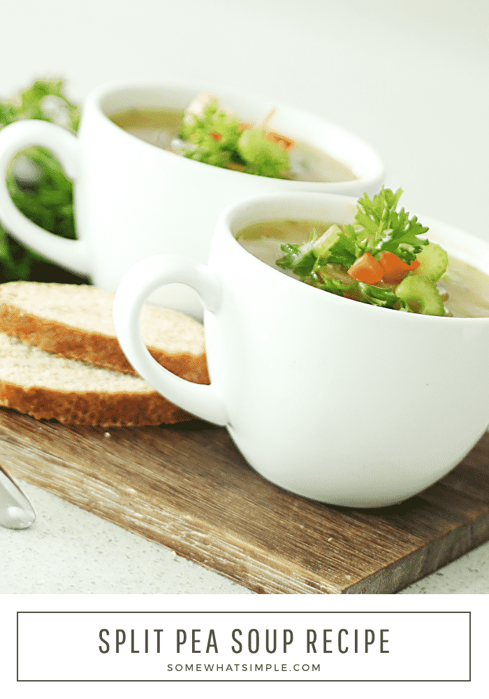 two white cups of split pea soup topped with chopped carrots, celery and parsley. The cups are sitting on a wood cutting board, next to the cups, are two slices of bread. The words split pea soup recipe are in written in a white box at the bottom of the image.