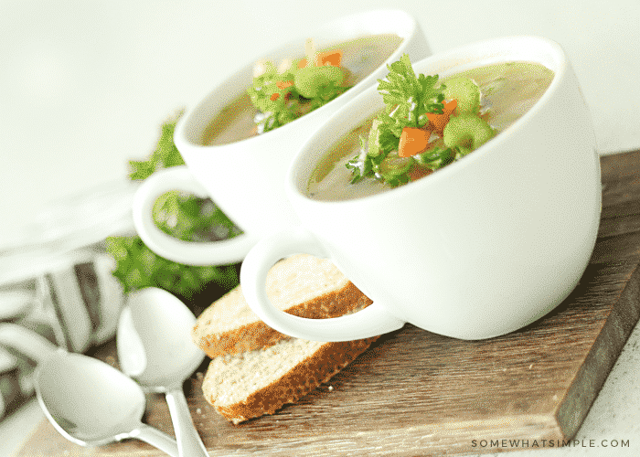 two white cups of split pea soup topped with chopped carrots, celery and parsley. The cups are sitting on a wood cutting board, next to the cups, are two slices of bread.