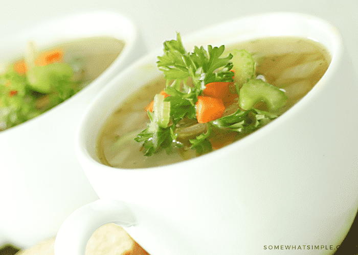a close up picture of a white cup filled with split pea and ham soup that is topped with chopped carrots, celery and parsley. A second cup is in the background.