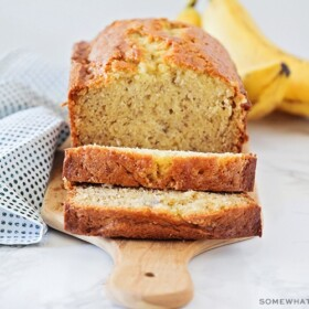 a loaf of homemade banana bread made with this easy recipe . Two slices have been cut off from one end and are laying down on the cutting board. Behind the loaf of bread is a small bunch of bananas.