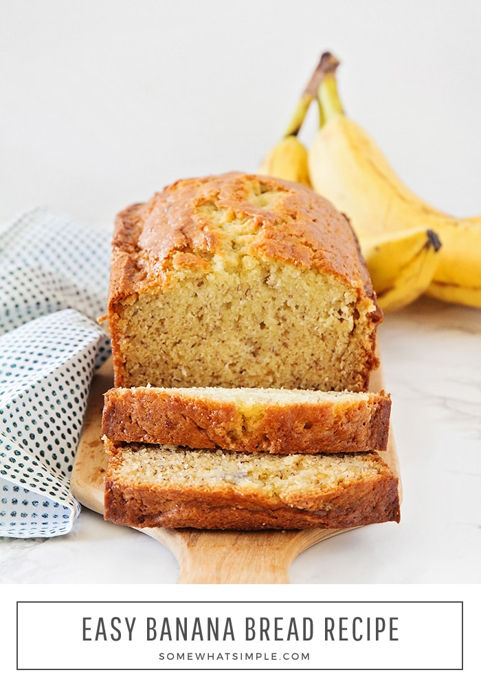 a loaf of banana bread made with the classic recipe sitting on a wood cutting board. The loaf has two slices cut off the front. At the bottom of the image in a white box, the words easy banana bread recipe are written in black.