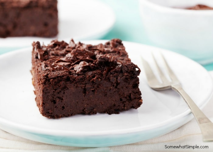the best brownies on a white plate with fork
