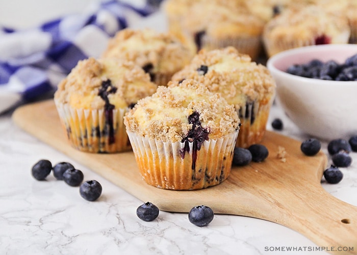 several homemade blueberry muffins on a counter topped with a delicious cinnamon crumble