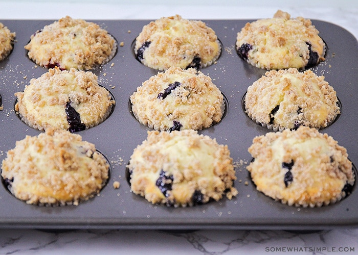 a muffin tin filled with the best blueberry muffins that are fresh out of the oven and have a crumb topping