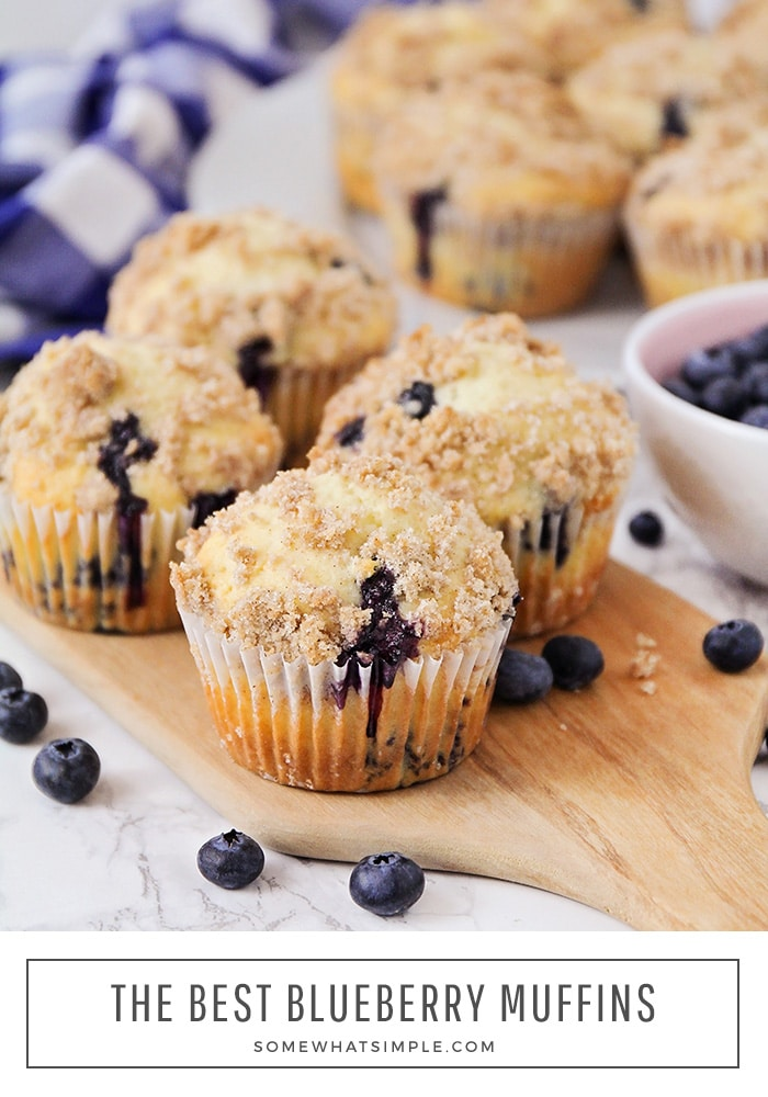 a close up of four blueberry muffins made with this easy recipe. There's a bowl of fresh blueberries next to the muffins and a few blueberries have been scattered on the counter. In the background is a white plate full additional muffins. At the bottom of the image the words The Best Blueberry Muffins is written in a white box.