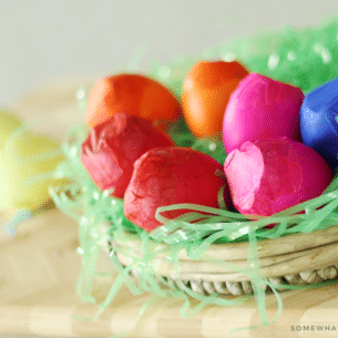 a shallow basket with green plastic Easter grass that is filled with red, pink, orange and blue cascarones