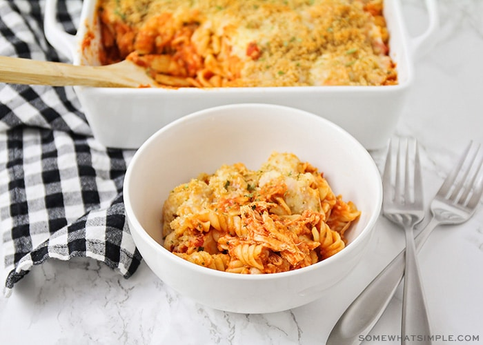 a white bowl filled with a serving of chicken parmesan casserole that is made with pasta and topped with bread crumbs and cheese. Behind the bowl on the counter is a casserole pan filled with the remaining casserole.