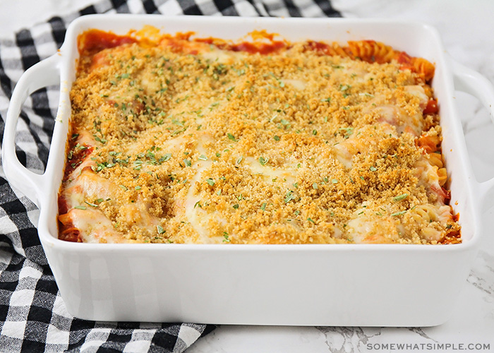 a casserole pan filled with this easy chicken parmesan casserole recipe. The casserole is fresh from the oven with golden brown bread crumbs on top and parsley sprinkled on top.