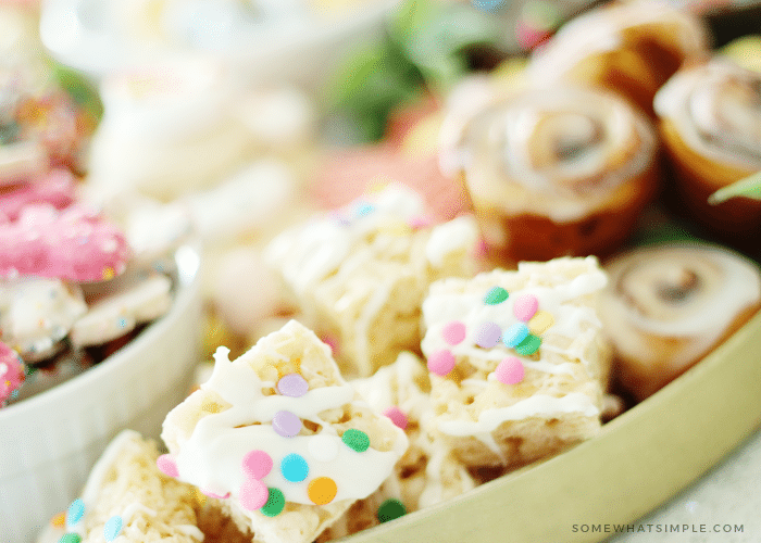 a close up of squared sugar cookie bars with pastel sprinkle dots with other cookies in the cookie tray in the background.