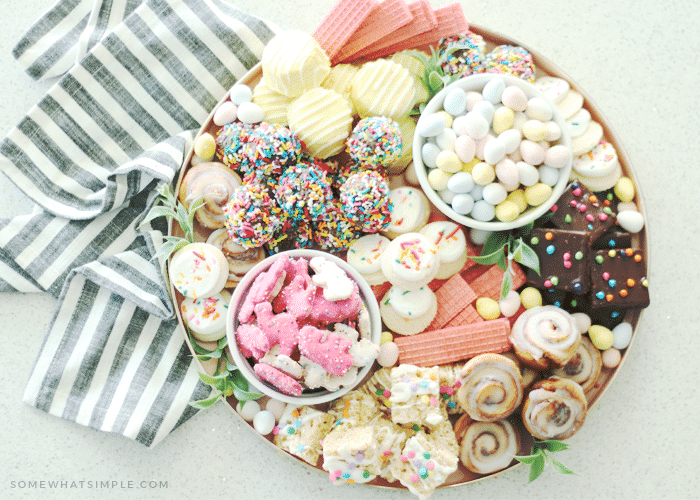 looking down on an Easter dessert tray filled with an assortment of brightly colored cookies and desserts.
