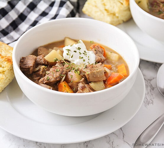 a white bowl filled with savory crock pot beef stew. There are chunks of beef and chopped potatoes and carrots topped with a dollop of sour cream and chopped parsley. The bowl is sitting on a white plate with a square of bread next to it. Above the bowl is a black and white checkered cloth napkin and in the corner of the image another bowl of stew is partially visible.