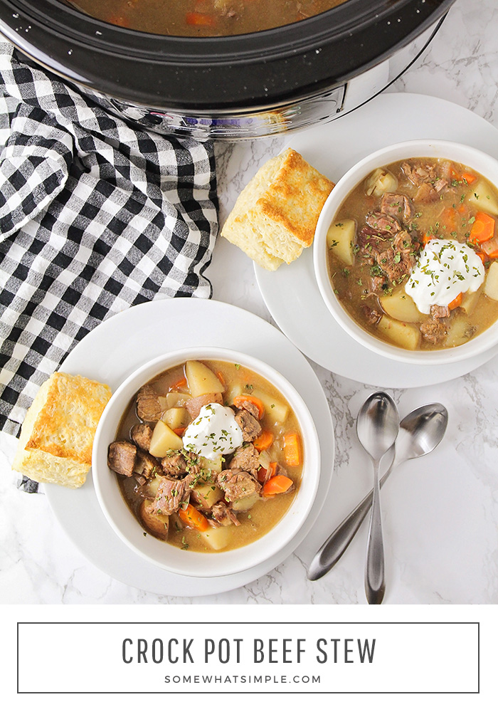looking down on two bowls filled with beef stew that was made in a crock pot. Both bowls are topped with sour cream and both have a slice of bread next to them. On the counter behind the bowls is a slow cooker filled with stew. At the bottom of the image the words Crock Pot Beef Stew are written in a white box.