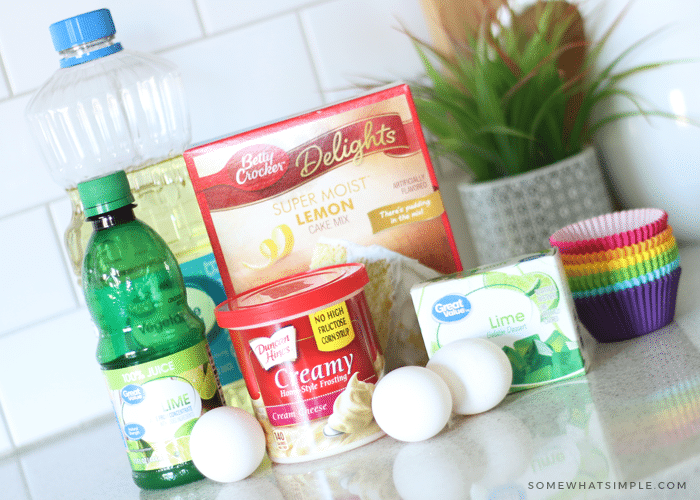 the ingredients needed to make key lime cupcakes are sitting on the counter and they include; lime juice, lime jello, cupcake toppers, cake mix and frosting