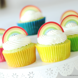a close up of Key Lime Cupcakes sitting on top of a white cake stand. The lime cupcakes are wrapped in different colored cupcake wrappers and topped with white frosting and a rainbow cupcake topper