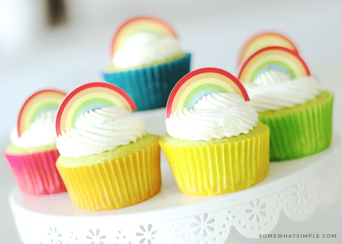 Key Lime Cupcakes sitting on top of a white cake stand. The lime cupcakes are wrapped in different colored cupcake wrappers and topped with white frosting and a rainbow cupcake topper