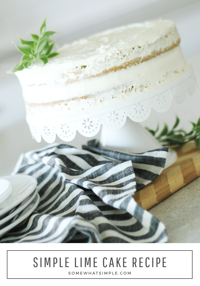 a key lime cake topped with a white frosting sitting on a white cake stand with a black and white striped cloth napkin laying on the counter below the cake. the words simple lime cake are written at the bottom of the image.