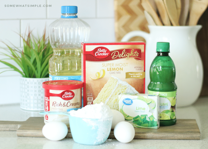 the ingredients to make a key lime cake sitting on a counter which include, lime juice, lime jello, cake mix, frosting and eggs