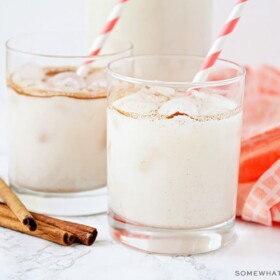 two glasses filled with this easy horchata recipe. Each glass has a red and white striped straw in it. Next to the glasses are 4 cinnamon sticks laying on the counter as well as a light red cloth napkin.